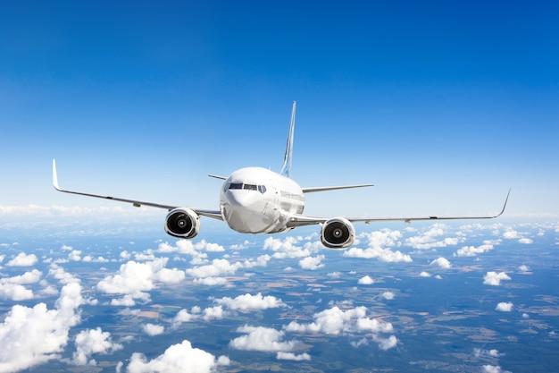 Flugzeug fliegt über die sommerwolken und die erdoberfläche unter dem blauen himmel.