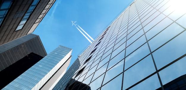 Flugzeug fliegt über moderne glasgebäude wolkenkratzer im finanzviertel der stadt
