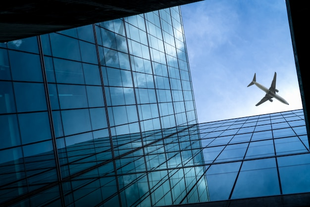 Flugzeug fliegt über modernem glasbürogebäude. perspektivische ansicht des futuristischen glasgebäudes. außenansicht des büroglasgebäudes. geschäftsreise. firmenfenster.