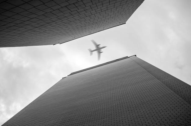 Flugzeug fliegt über wolkenkratzer. ansicht von unten.