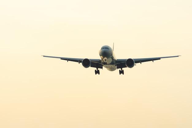 Flugzeug fliegt zum flughafen während des sonnenuntergangs.