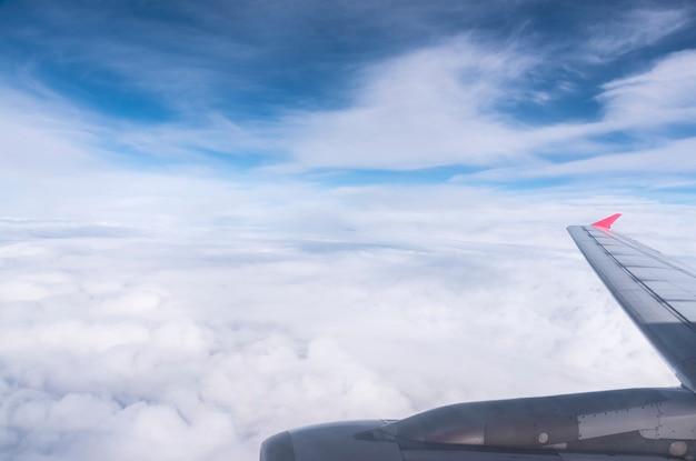 Flugzeug flügel in den blauen himmel mit wolken