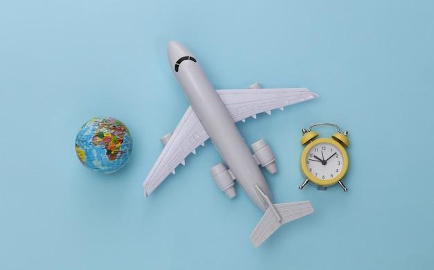 Flugzeug, globus und wecker auf blauem hintergrund.