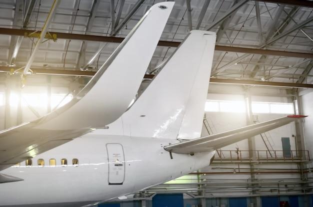 Flugzeug im hangar, blick auf tragflächen und leitwerk.