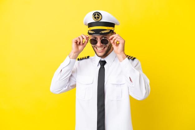 Flugzeug kaukasischer pilot auf gelbem hintergrund mit brille isoliert und überrascht