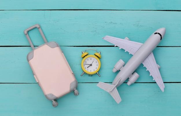 Flugzeug, mini-reisegepäck und wecker auf blauem holzhintergrund. zeit zu reisen.