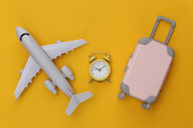 Flugzeug, mini-reisegepäck und wecker auf gelbem hintergrund.