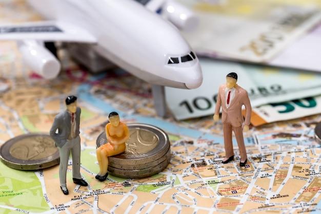 Flugzeug mit karte, euro und miniaturspielzeugmenschen