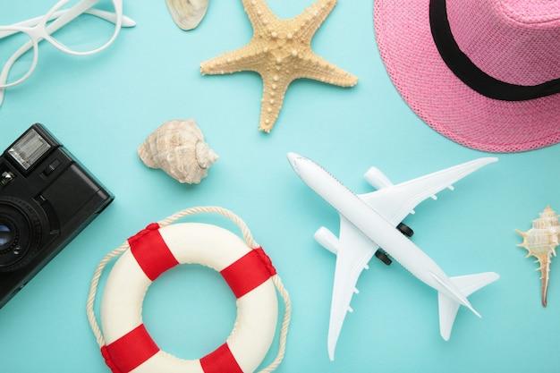 Flugzeug mit reiseaccessoires an blauer wand. reisekonzept. draufsicht