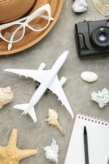 Flugzeug mit reiseaccessoires an grauer wand. reisekonzept.