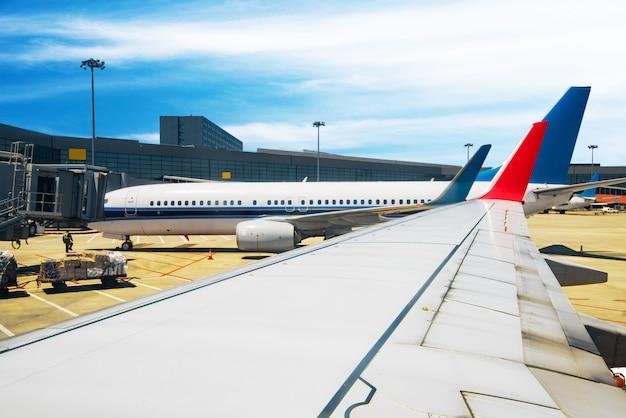 Flugzeug nahe dem terminal in einem flughafen bei dem sonnenuntergang.
