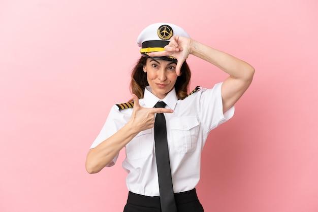 Flugzeug pilotin mittleren alters isoliert auf rosa hintergrund mit fokussierung gesicht. rahmensymbol