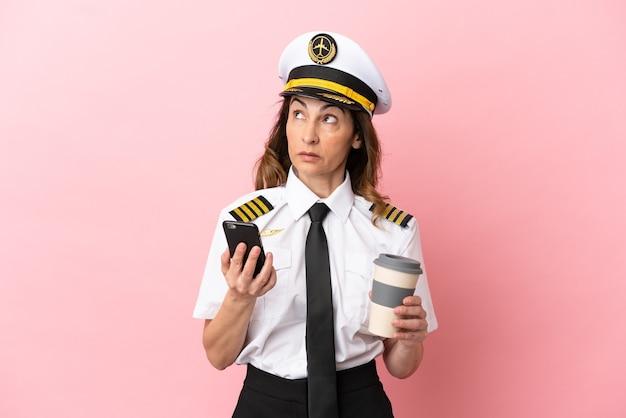 Flugzeug pilotin mittleren alters isoliert auf rosa hintergrund mit kaffee zum mitnehmen und einem handy, während sie etwas denkt