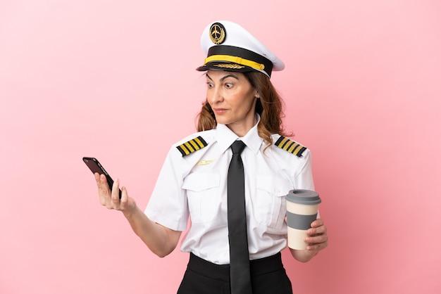 Flugzeug pilotin mittleren alters isoliert auf rosa hintergrund mit kaffee zum mitnehmen und einem handy