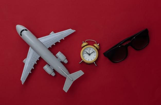 Flugzeug, sonnenbrille und wecker auf rotem grund. zeit zu reisen.