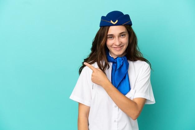 Flugzeug-stewardess-frau isoliert auf blauem hintergrund, die auf die seite zeigt, um ein produkt zu präsentieren