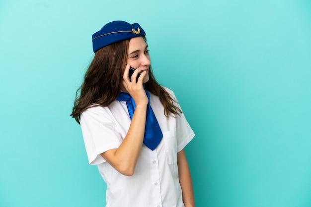 Flugzeug-stewardess-frau isoliert auf blauem hintergrund, die ein gespräch mit dem mobiltelefon mit jemandem führt