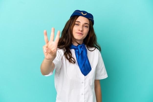 Flugzeug-stewardess-frau isoliert auf blauem hintergrund glücklich und zählt drei mit den fingern