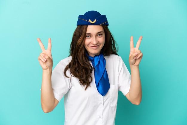 Flugzeug-stewardess-frau isoliert auf blauem hintergrund mit victory-zeichen mit beiden händen