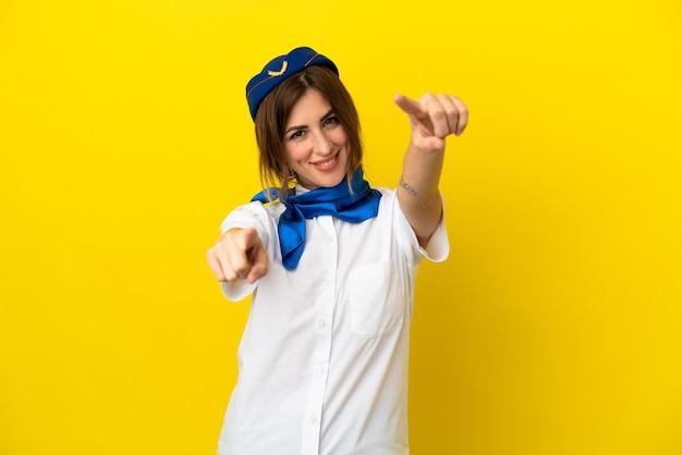 Flugzeug-stewardess-frau isoliert auf gelbem hintergrund zeigt mit dem finger auf sie, während sie lächelt Premium Fotos
