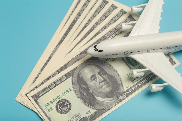 Flugzeug und geldflugzeug vor dem hintergrund von us-dollar die kosten für flugtickets und flüge...