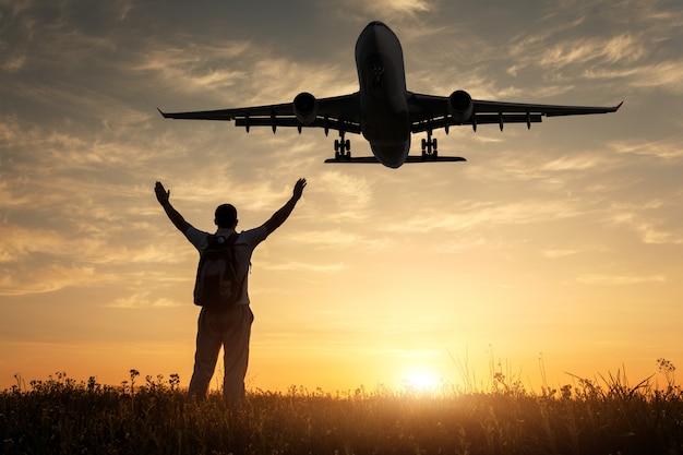 Flugzeug und silhouette eines stehenden glücklichen mannes