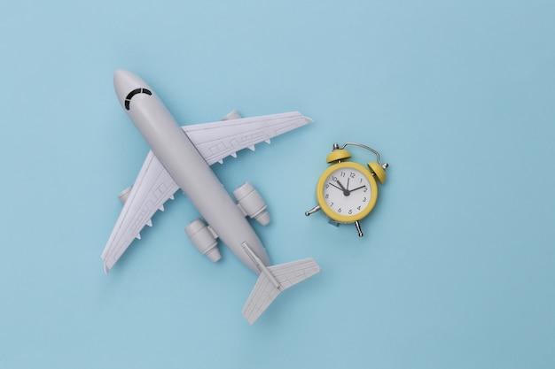 Flugzeug und wecker auf blauem hintergrund.