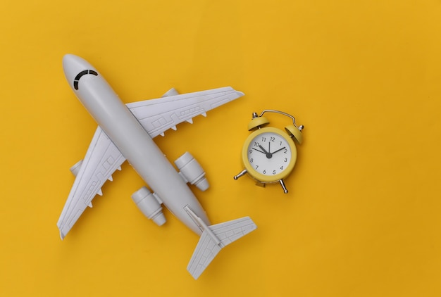 Flugzeug und wecker auf gelbem hintergrund.