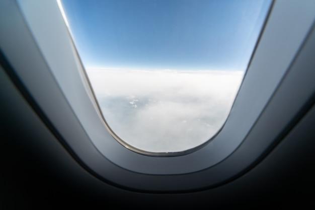 Flugzeugfensteransicht zum bewölkten himmel und zur erde