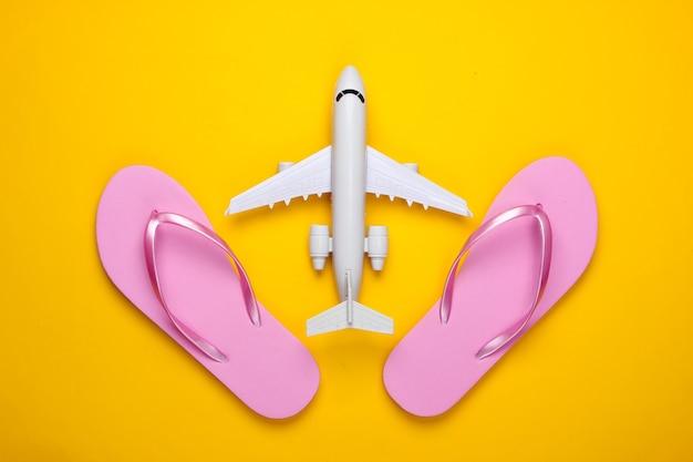 Flugzeugfigur, flip flops auf gelb. strandurlaub.