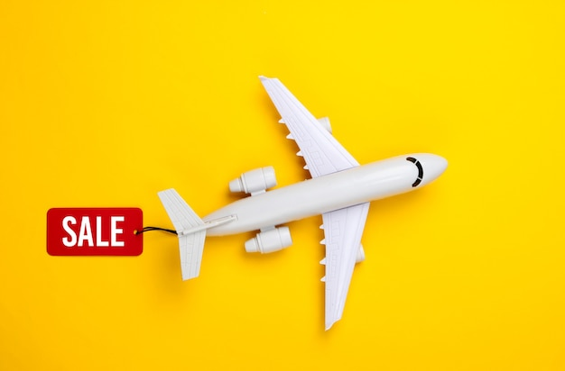 Flugzeugfigur mit rotem verkaufsetikett auf gelb.