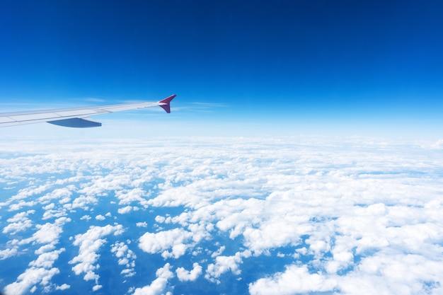 Flugzeugflügel auf dem blauen himmel und den wolken