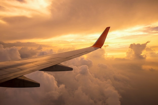 Flugzeugflügel auf den wolken des sonnenuntergangs