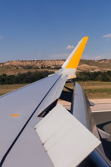 Flugzeugflügel auf der landebahn am flughafen an einem sonnigen tag. klappen hoch. reise- und urlaubskonzept. blick aus dem passagierfenster