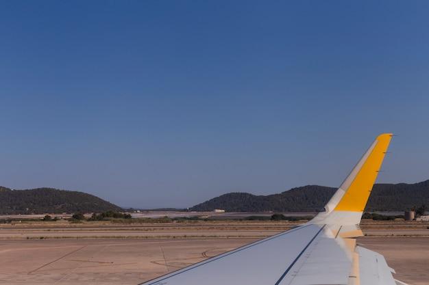 Flugzeugflügel auf der landebahn am flughafen an einem sonnigen tag. reise- und urlaubskonzept. blick aus dem passagierfenster