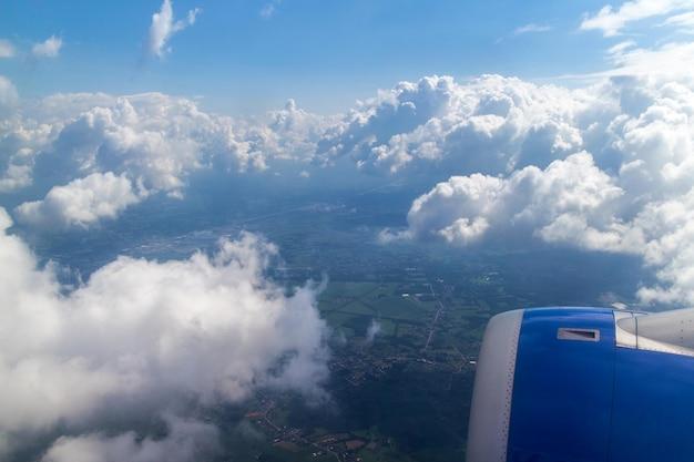 Flugzeugflügel fliegt über weiße wolken