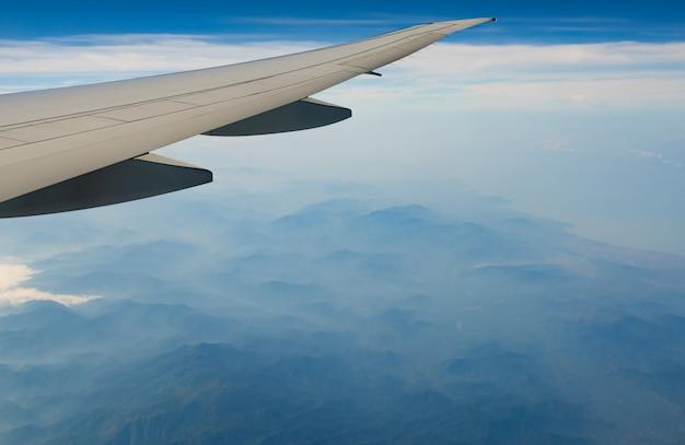 Flugzeugflügel über berg. flugzeug fliegt auf blauem himmel und weißen wolken. szenische ansicht vom flugzeugfenster. kommerzieller flug. flugzeugflügel.