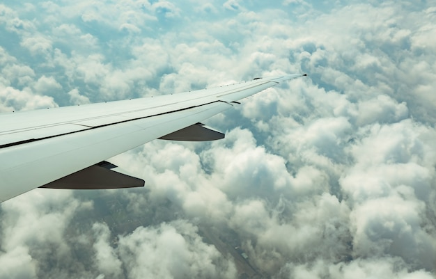 Flugzeugflügel über weißen wolken. flugzeug fliegt auf blauem himmel. szenische ansicht vom flugzeugfenster. kommerzieller flug. flugzeugflügel über wolken.