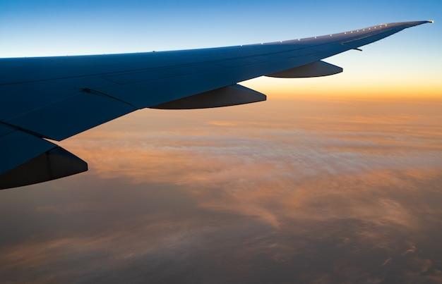 Flugzeugflügel über weißen wolken. flugzeug fliegt auf sonnenaufgang himmel. szenische ansicht vom flugzeugfenster. kommerzieller flug. flugzeugflügel über wolken.