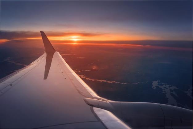 Flugzeugflügel während eines vibrierenden sonnenuntergangs