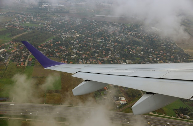 Flugzeugflügelansicht vom flugzeug zum himmel, wolken, erde aus einer flughöhe.