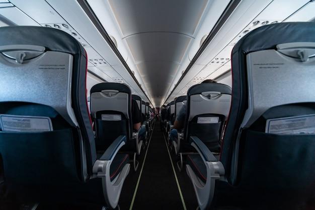 Flugzeugkabinensitze mit passagieren. economy class der neuen günstigsten billigfluggesellschaften ohne verspätung oder flugstornierung. reise in ein anderes land.