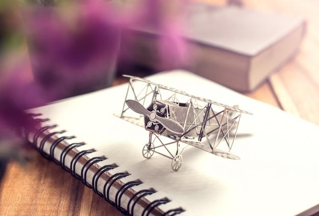 Flugzeugkämpfer auf offenem bildungsbuch mit abstraktem licht