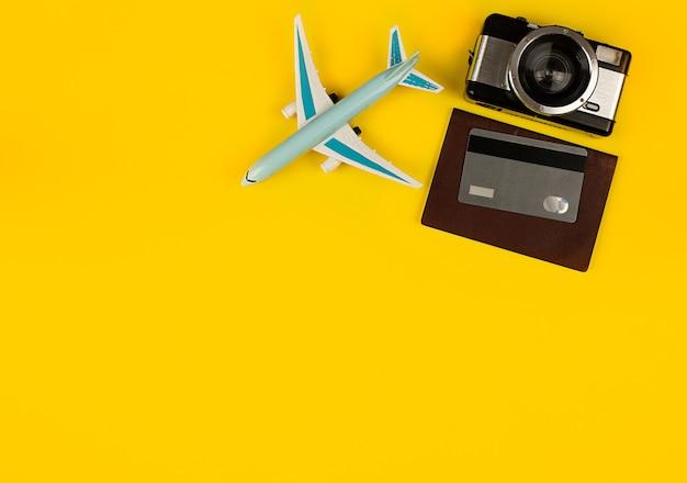 Flugzeugminiatur als symbol für reisekamera und reisepass reisezubehör kreditkarte