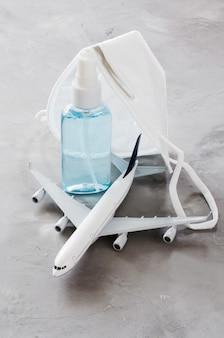 Flugzeugmodell, gelflaschenspray und gesichtsmaske