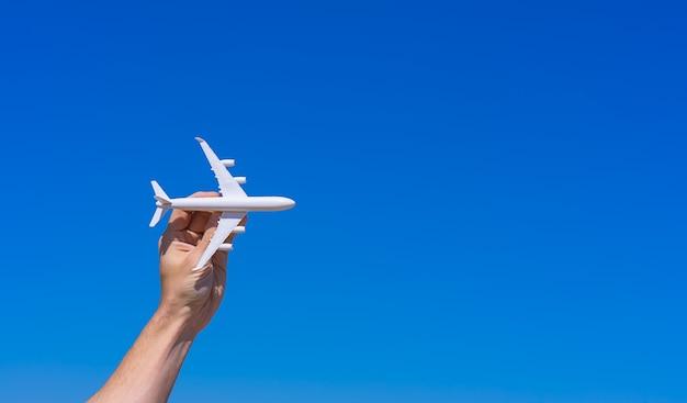 Flugzeugmodell in der hand gegen klaren blauen himmel