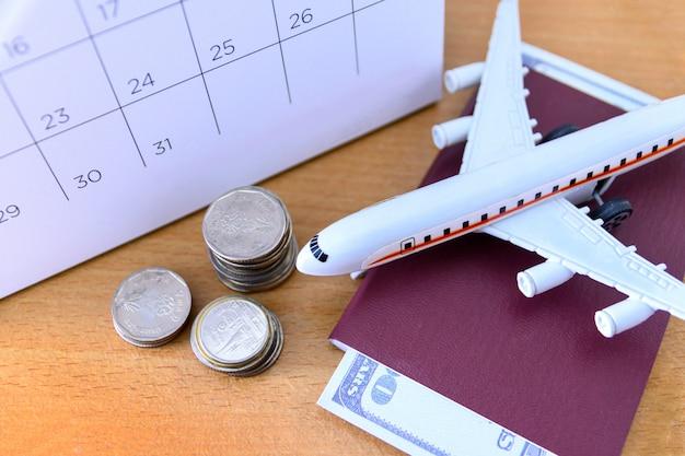 Flugzeugmodell mit papierkalender auf holztisch. reiseplan