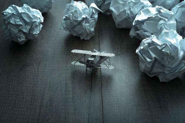 Flugzeugmodell mit zerknittertem papier auf hölzernem hintergrund. geschäftsfrustrationen, arbeitsstress und nicht bestandene prüfung.