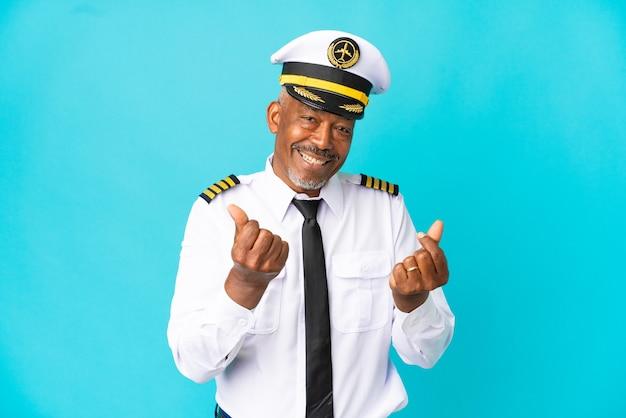 Flugzeugpilot älterer mann isoliert auf blauem hintergrund macht geldgeste Premium Fotos