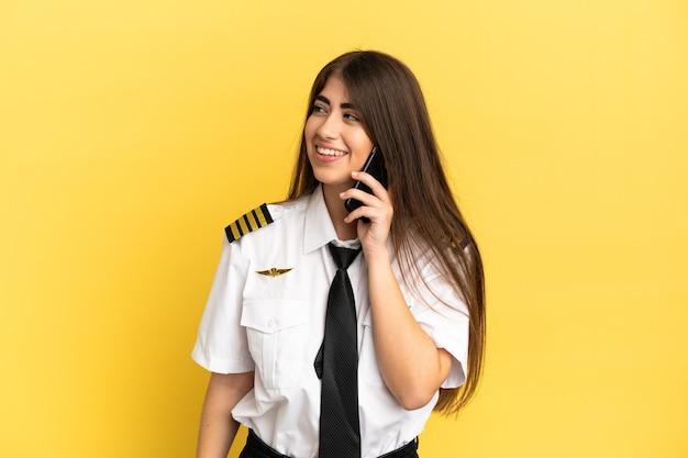 Flugzeugpilot isoliert auf gelbem hintergrund, der ein gespräch mit dem mobiltelefon mit jemandem führt